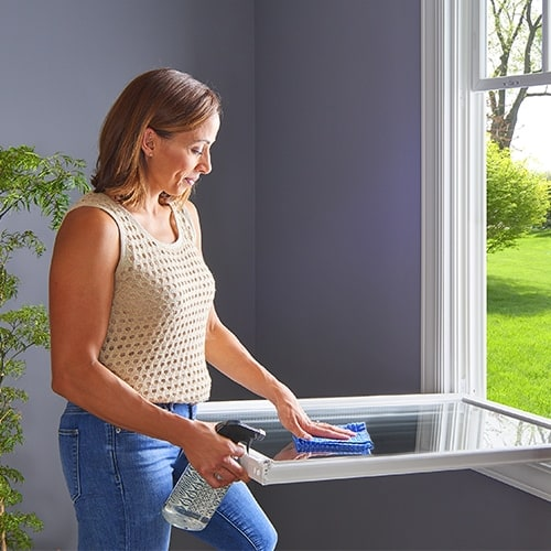 woman cleaning a window